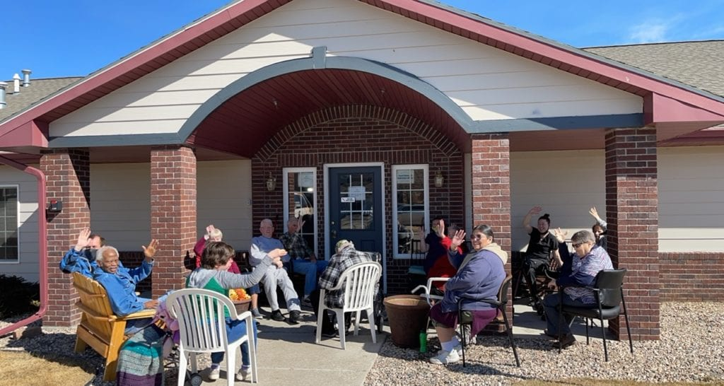 group of seniors sitting on patio waving at camera