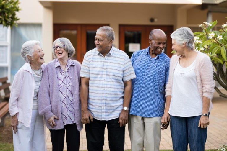 Cheerful senior men and women standing at retirement nursing home