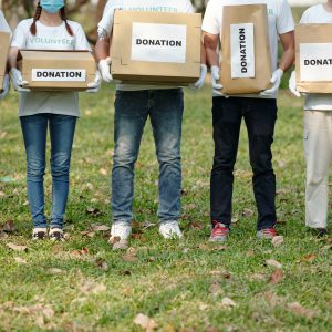 Cropped image of volunteers with donation boxes full of clothes and groceries standing park